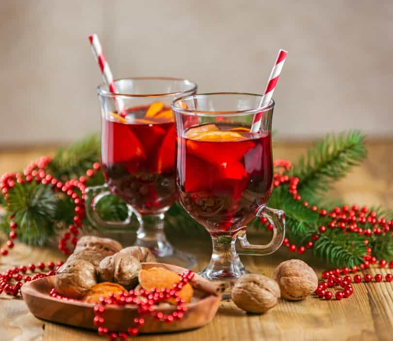 Two glasses of mulled wine for Christmas and winter holidays on the wooden table.